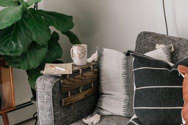 diy rustic decor wood tabletop with mug and calendar on gray sofa with pillows next to plant