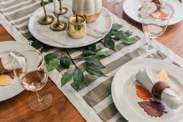 Minimalist striped table runner with plates decorated with paper leaves
