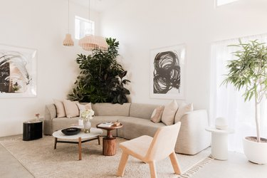 a sunken living room with a curved sectional couch, large potted plants, and two mid-century coffee tables,