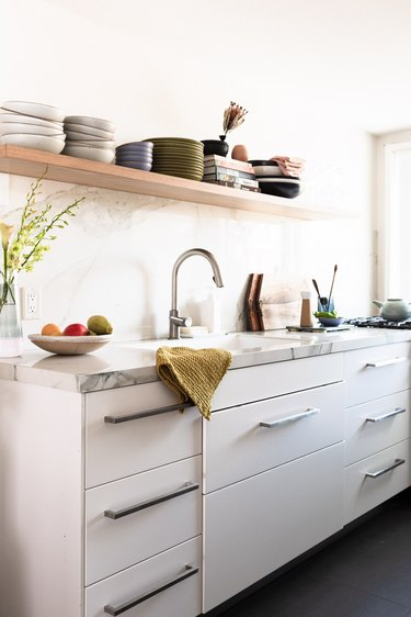 a kitchen with white drawer fronts below, marble countertops, and open shelving above