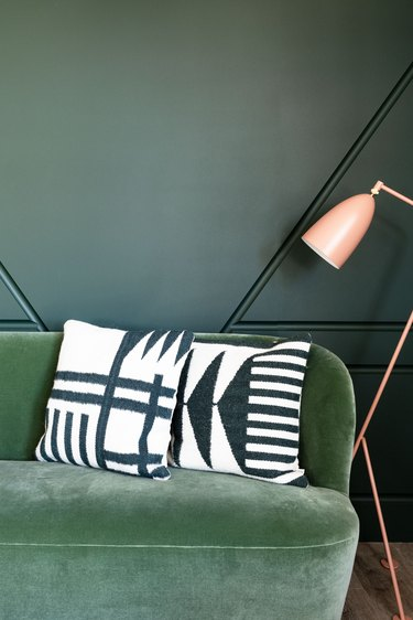 color scheme with a medium-green couch against a dark green wall next to a pink floor lamp