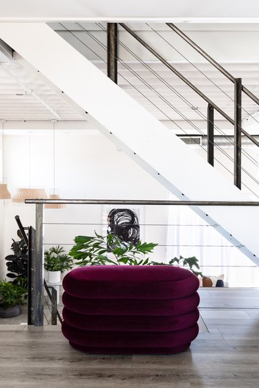 a large burgundy pouf under a white staircase