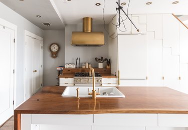 A white kitchen island with a wood counter and brass faucet sink. A brass hood over a stovetop and wood counter.