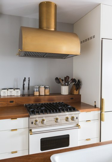 Brass stove hood over a stovetop. White cabinets with a wood counter and brass handles. Containers, sculptures, and utensils on a ledge.