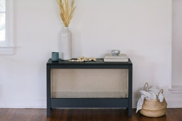 Black sideboard with cane and wicker basket on wood floor
