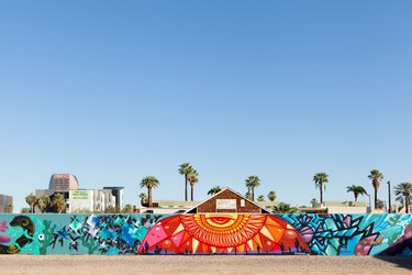 A colorful red, blue, and yellow mural with surrounding buildings and palm trees