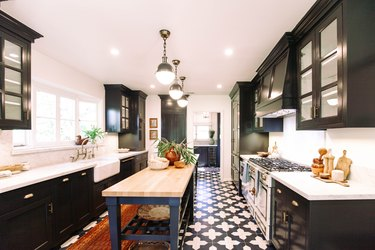 Kitchen with black cabinets, globe pendant lights, ornate tile floor and kitchen island with wood tabletop