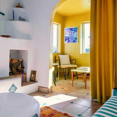 Modern Spanish-style room with white fire alcove in living room, yellow side room with chairs, and white and green tiling