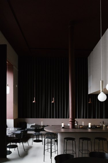 Dark minimalist bar with dark brown and black dining furniture and pendant lights