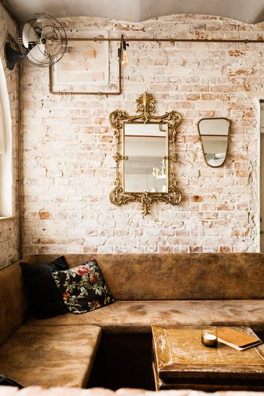 rustic industrial decor with brown leather booth against light brick wall with mirrors