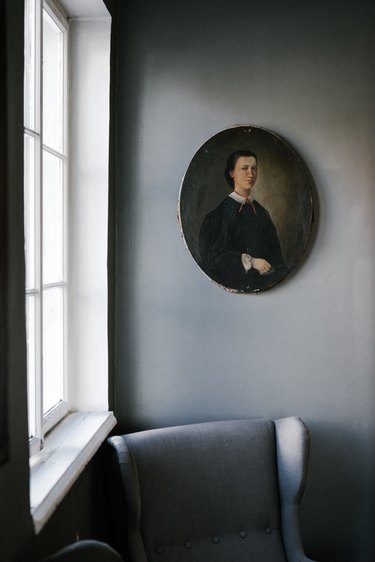 Vintage painting over gray accent chair by window
