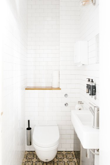 Minimalist bathroom with white tiled walls and neutral mosaic tile floors