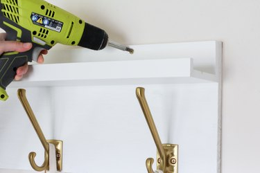 Hand screwing white kitchen wall hangers with gold hooks onto white wall with gold screws