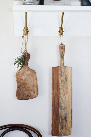 White kitchen wall hangers with gold hooks holding cutting boards against white wall