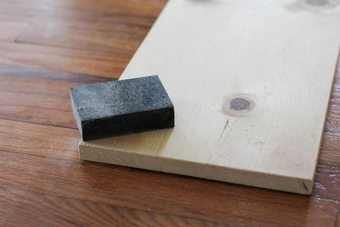 Sanding block resting on flat piece of plywood on wood flooring