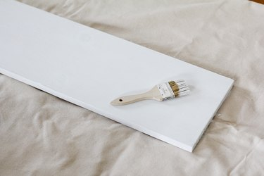 White painted board resting on canvas sheet with white paintbrush