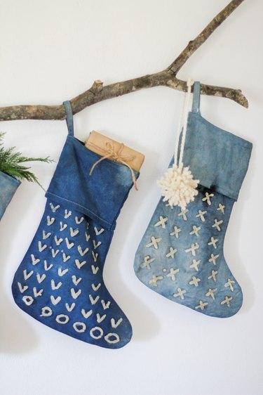Two indigo stocking and decorative branch