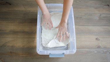 Hands placing stocking in a bucket of water to prepare for indigo dye