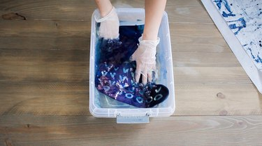 Gloved hands rinsing indigo dye on a stocking in a bucket of water