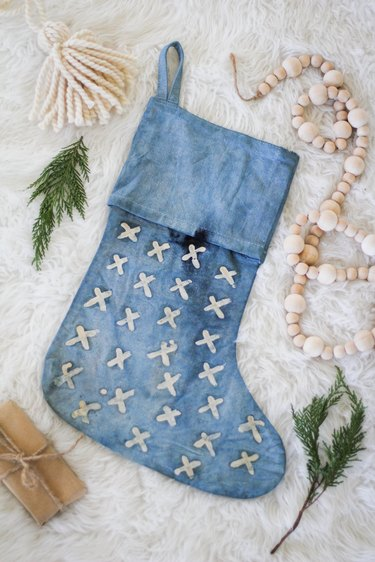 Indigo stocking with stitched white x's surrounded by decorative fir and decorations