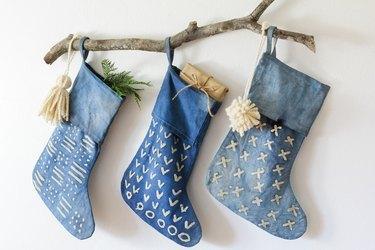 Three indigo stockings with decorative branch