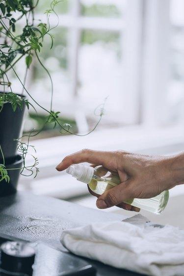 using a spray bottle full of lemon-vinegar solution to clean a countertop