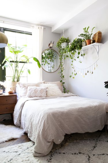 Farmhouse Chic Bedroom Ideas in Bedroom with plants, round mirror, gold moon banner, wood night stand, and pink-white bedding.