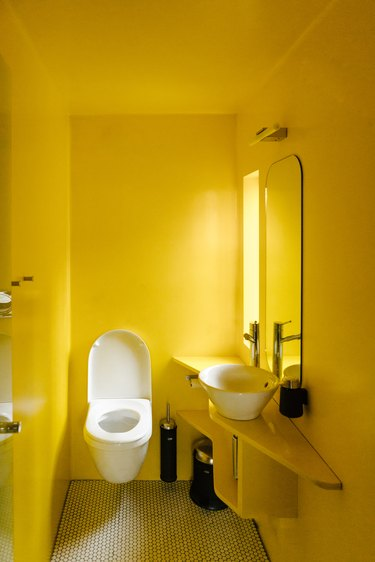 Minimalist yellow-walled bathroom with sink, mirror, window and white tile floorToilet in bathroom.