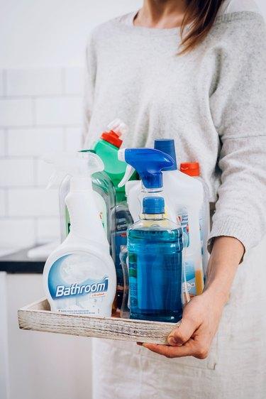 Hands holding tray of liquid bottles