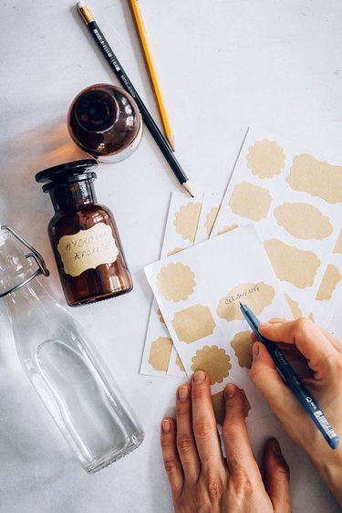 Hand painting gold sticker label sheets for cleaning bottles next to pencils