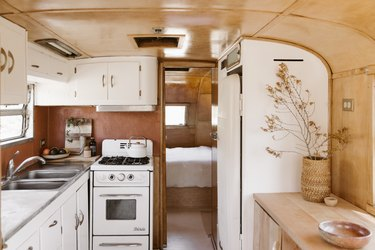 Interior of a camper with a white cabinet kitchen, Southwest rug, retro refrigerator, stools, wood table, basket vase with dried flowers.