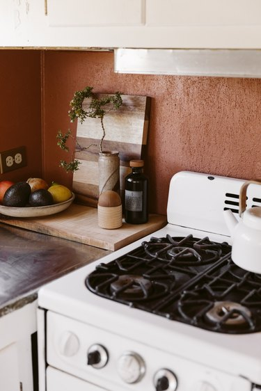 Kitchen corner with a small stove, dish of fruit, wood cutting boards, and vase with a plant clipping.