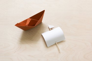 Folded brown paper boat with sail made from paper and a toothpick