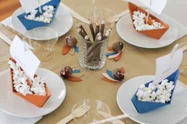 Kids table with folded paper boats, thanksgiving decorations, disposable dishware