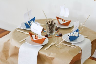Kids table with folded boat decorations and disposable dishware