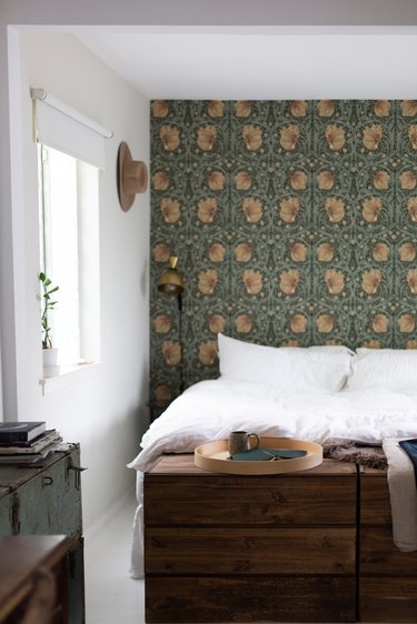 Bedroom with floral Art Nouveau wallpaper. A wood dresser, vintage trunk, and round wood tray.