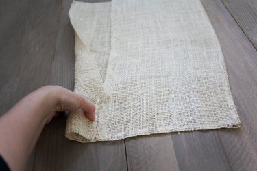 Hand folding burlap sheet to create pocket for dowel