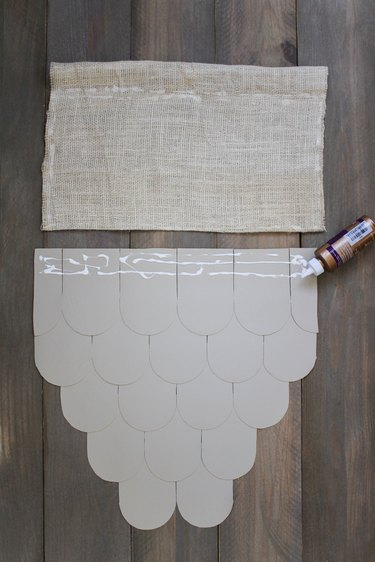 Leather scallops with applied fabric glue and burlap on wood background