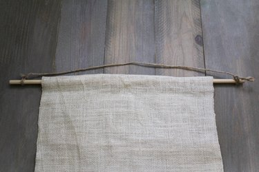 Burlap sheet hanging on wood dowel with twine for hanging