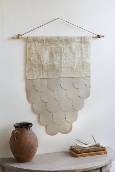 Leather-burlap wall hanging over half-moon table with decorative vase