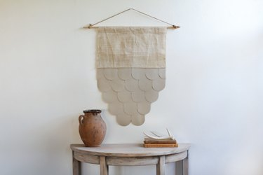 rustic decor with leather-burlap wall hanging over half-moon table with decorative vase