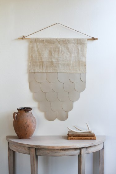 Burlap-leather wall hanging over half-moon table with decorative vase