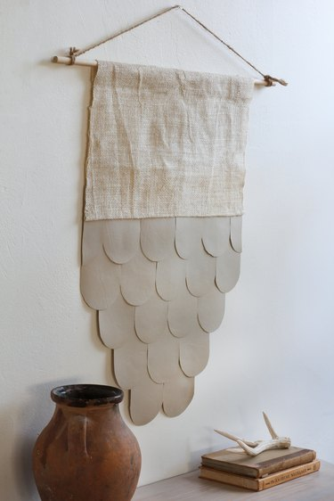Boho leather and burlap wall hanging on white wall with decorative vase