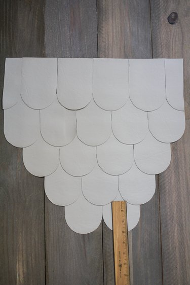 Leather scallops with ruler on wood floor