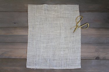 Burlap sheet wit gold scissors on wood background