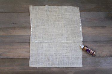 Burlap sheet with fabric glue on wood background