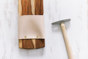 a tack hammer and a cutting board with leather strips attached with tacks
