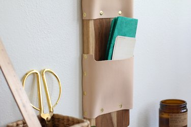 a wall-mounted letter holder made from a cutting board and leather strips