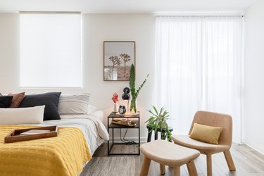 Bedroom with nightstand, beige chair, yellow-white bedding and plants