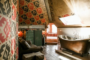 a bathroom with a distressed wood floor, a worn leather couch, and a metal claw-foot tub under a skylight